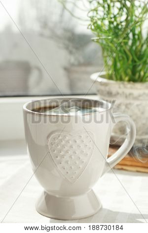 Cup of delicious coffee on window sill