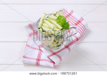 cup of zucchini strips on checkered dishtowel