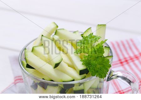 cup of zucchini strips on checkered dishtowel - close up
