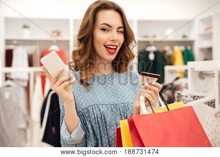 Attractive woman with smartphone and packages winking to camera in store