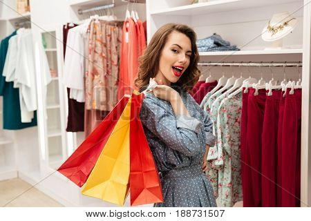 Pretty smiling woman winking in shop of woman clothes