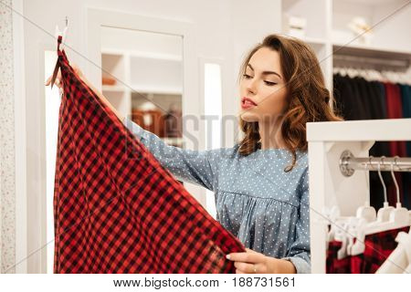 Picture of concentrated woman shopper in blue dress choosing clothes in shop. Looking aside.