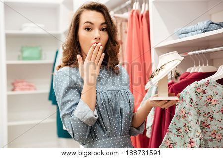 Picture of shocked young woman shopper in blue dress in shop choosing clothes. Looking aside.