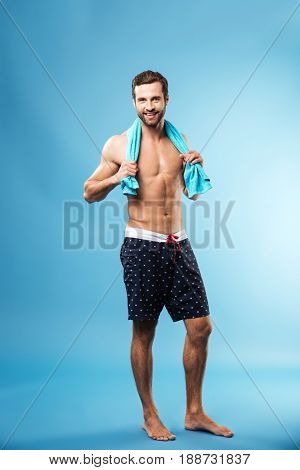 Full-length portrait of young bearded man standing over blue in swimwear with towel