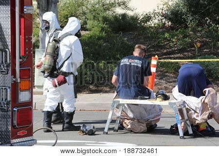 Lake Forest, California, May 23, 2017: Hazardous materials team, cleans up a single truck accident containing swimming pool chemicals, preventing poisonous liquids from release into the environment.