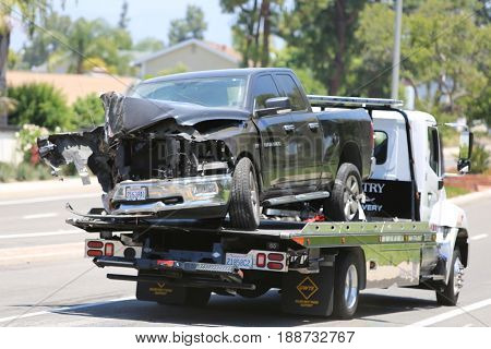 Lake Forest, California, May 23, 2017: A flat bed tow truck removes and halls away a  pool service truck after causing an accident causing Hazmat to respond and clean up hazardous chemicals.