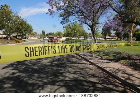 Lake Forest, California, May 23, 2017: Sheriff's Line DO NOT CROSS yellow caution tape secures a Hazardous Clean Up Accident Scene as a HAZMAT team cleans up dangerous chemicals.