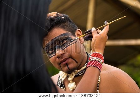 Native Brazilian man from Tupi Guarani tribe having his face painted, Brazil