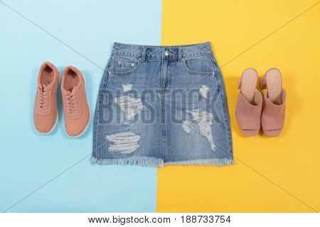 Blue denim skirt with shoes isolated yellow and blue  background