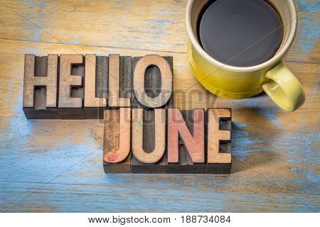 Hello June- word abstract in vintage letterpress wood type blocks against grunge wooden background with a cup of coffee