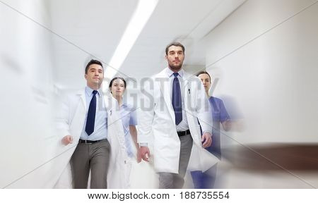 people, health care and medicine concept - group of medics walking along hospital (motion blur effect)