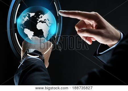 business, people, mass media and technology concept - close up of businessman hands with smartwatch and earth hologram over black background
