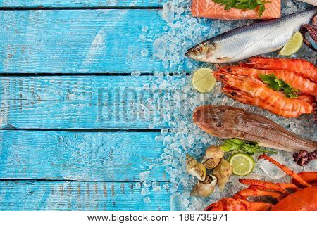 Many kind of seafood, crab, mussels, prawns, fish, salmon steak, mackerel and other shells served on crushed ice and wooden table