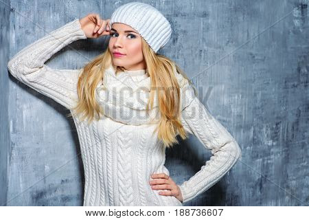 Winter beauty, cosmetics. Beautiful blonde girl wearing white winter clothes smiling at camera. Winter fashion concept.