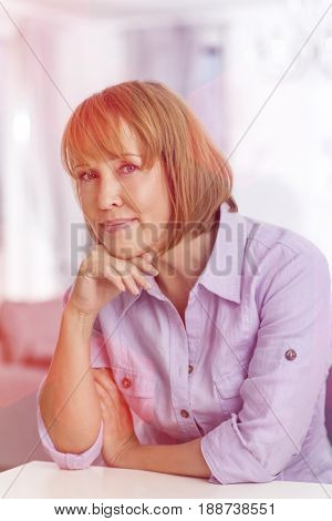 Portrait of mature woman with hand on chin sitting at table in house