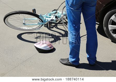 Man checking consequences of car and bicycle accident on street