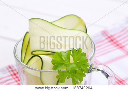 cup of raw zucchini strips on checkered dishtowel - close up