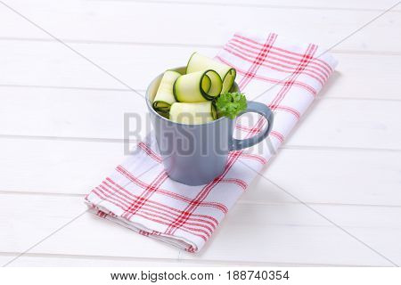 cup of raw zucchini strips on checkered dishtowel