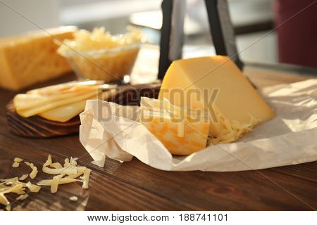 Different cheese and grater on table
