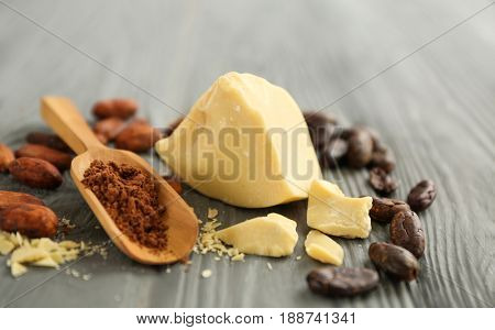 Composition with cocoa butter, powder and beans on wooden background