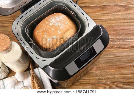 Fresh crusty loaf in bread maker on wooden background