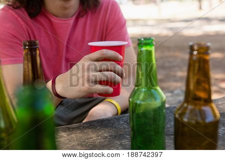 Mid-section of man holding a disposable glass of beer in the park