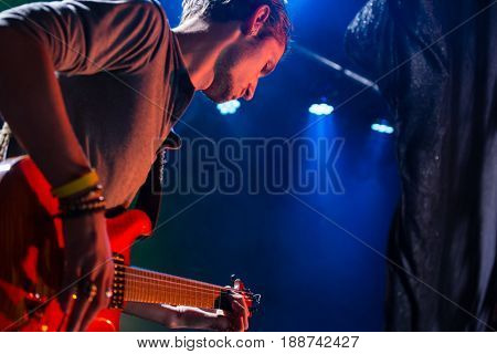 Guitarist playing guitar on stage in nightclub