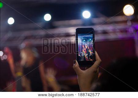 Audience recording video of band on mobile phone in nightclub