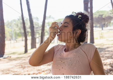 Young woman using asthma inhaler in the park