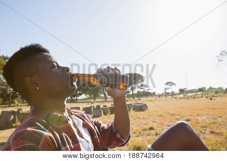 Young man having a beer in the park on a sunny day