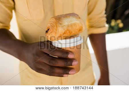 Mid section of man holding disposable coffee cup with bread