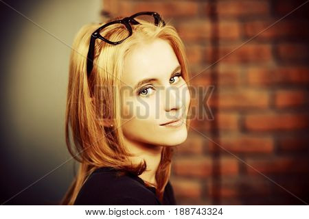 Portrait of a beautiful young woman wearing glasses. Optics style.