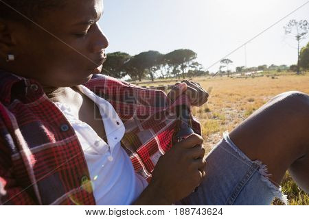 Man opening the lid of beer bottle on a sunny day