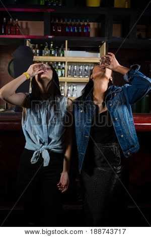 Female friends having tequila shot at bar counter