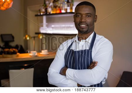 Portrait of confident waiter standing with arms crossed in restaurant