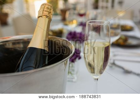 Close up of champagne bottle in bucket with glass on table in restaurant