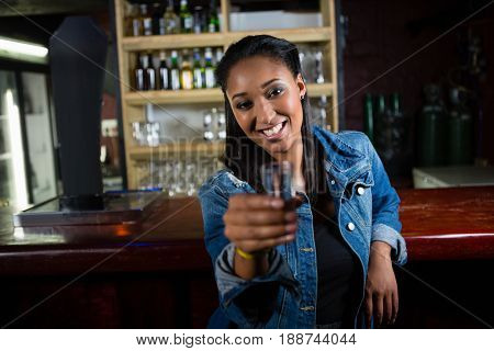 Portrait of happy woman having tequila shot at bar counter