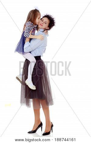 Happy young beautiful mother, lifted his little beloved daughter .And the girl kisses his mother on the cheek.Isolated on white background.