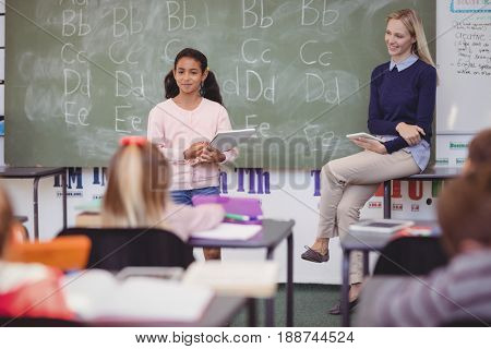 Schoolgirl taking lesson of her classmates in school