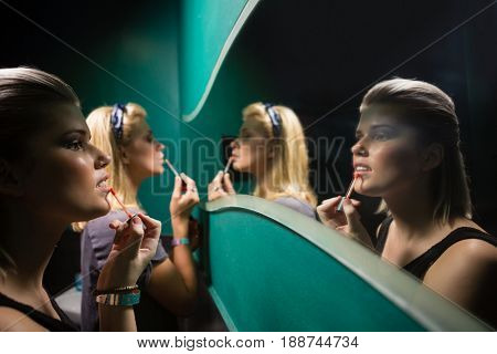 Two women applying lip gloss while looking at mirror in washroom