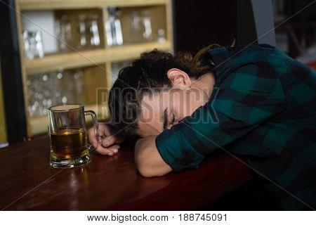 Drunk man sleeping on bar counter