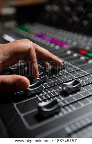 Hand of male audio engineer using sound mixer in recording studio