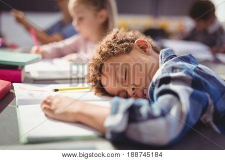 Tired schoolboy sleeping in classroom at school