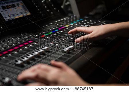 Hands of female audio engineer using sound mixer in recording studio