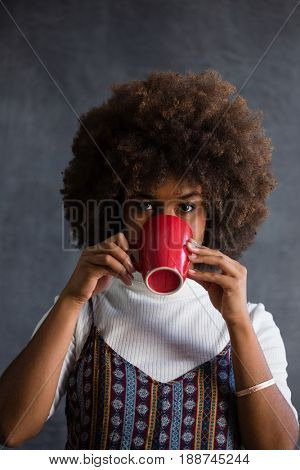 Portrait of woman with frizzy hair drinking coffee against wall