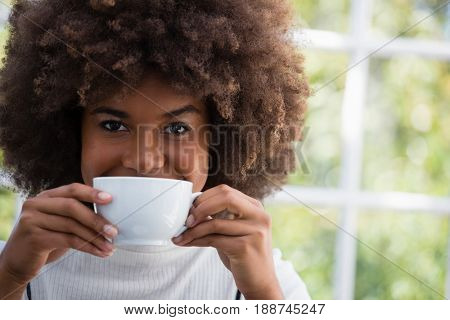 Close up portrait of smiling woman with frizzy hair having coffee in cafe