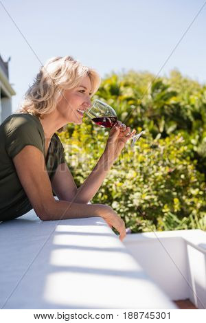 Side view of mid adult woman drinking red wine while leaning on retaining wall in restaurant