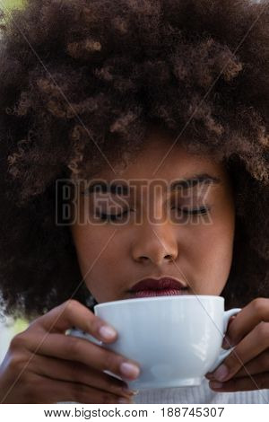 Close up of young woman with frizzy hair smelling coffee in cafe