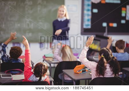 Schoolkids raising their hands in classroom at school