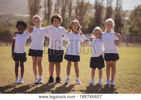 Portrait of happy schoolgirls standing with arms around in park on a sunny day